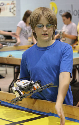 A student demonstrates the robot he built at the 2011 Dahlgren summer academy at Naval Surface Warfare Center Dahlgren Division. Photo Credit: Jake Joseph